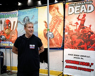Arthur Suydam, one of the artists for The Walking Dead, talks to visitors at the Youngstown Comic Con in Covelli Centre on Saturday afternoon. EMILY MATTHEWS | THE VINDICATOR