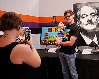Abbey Stiles, left, takes a photo of her husband Steve Stiles and their 7-month-old daughter Freya, all of Austintown, in front of pieces made by members of NeoLUG, a group of adult hobbyists who share their passion for building with Legos, at the Youngstown Comic Con in Covelli Centre on Saturday afternoon. EMILY MATTHEWS | THE VINDICATOR