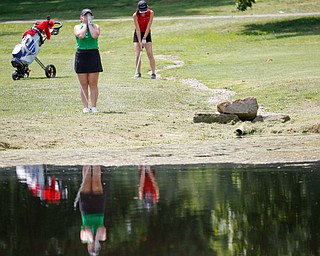 Hannah Ogden, 16, of Poland, left, reacts after hitting the ball while Grace Lee, 16, of Canfield, gets ready behind her during the Greatest Golfer junior qualifier at Salem Hills Golf Club on Tuesday. EMILY MATTHEWS | THE VINDICATOR