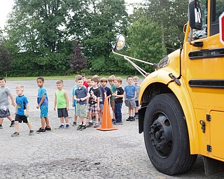 Incoming kindergarteners use what they learn about bus safety to cross in front of a bus as part of United Way's Success By 6 program at Stadium Drive Elementary on Tuesday morning. EMILY MATTHEWS | THE VINDICATOR