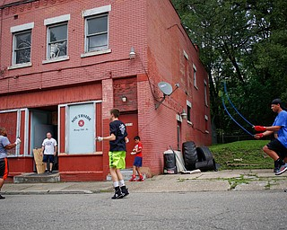 Jack Loew watches from the entrance of his boxing club as, from left, Bryan Gonzalez, Jackson Behun, Juan Jauregui, 10, and Deven Tate, all members of the Boxing Club, jump rope outside the club on Erie Street on Monday. EMILY MATTHEWS | THE VINDICATOR