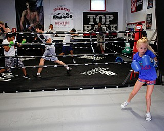 Zion Hensley, 9, right, and other members of Jack Loew's South Side Boxing Club, train at the club on Erie Street on Monday. EMILY MATTHEWS | THE VINDICATOR
