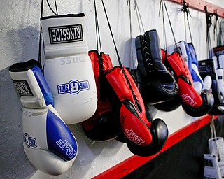Boxing gloves hang on the wall at Jack Loew's South Side Boxing Club on Erie Street. EMILY MATTHEWS | THE VINDICATOR
