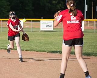 Emma Wolfe, left, tosses the ball to Katie McDonald at first as they practice with their Canfield-Poland softball team, who will be playing in the Junior League Softball World Series in Washington on Sunday. EMILY MATTHEWS   THE VINDICATOR