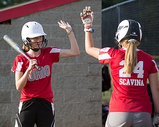 Emily Denney, left, and Alaina Scavina high-five as they practice with their Canfield-Poland softball team, who will be playing in the Junior League Softball World Series in Washington on Sunday. EMILY MATTHEWS   THE VINDICATOR