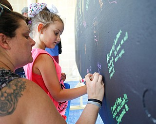 Amanda Humphreys, left, and her daughter Payge Humphreys, 6, both of Canfield, write a message for Amanda's brother-in-law Tyler, who passed away from a drug overdose, on a blackboard filled with written messages stating why people walk in the Warren Walk Against Heroin at the Warren Amphitheater on Sunday. EMILY MATTHEWS | THE VINDICATOR