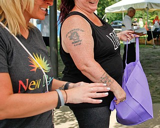 Tina Cvetkovich, right, who is 15 years into recovery and is a member of the Youngstown Board of Education, talks with Audra Olesky, of Howland, at the New Day Recovery table at the Warren Walk Against Heroin at the Warren Amphitheater on Sunday. EMILY MATTHEWS | THE VINDICATOR