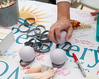 Dr. Michael Turkali, of McDonald and with New Day Recovery's on demand counseling, sets out stress balls at the New Day Recovery table at the Warren Walk Against Heroin at the Warren Amphitheater on Sunday. EMILY MATTHEWS | THE VINDICATOR