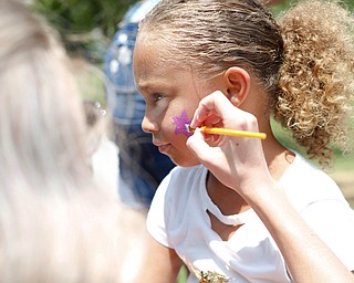 Serenity Kondilas, 6, of Columbus, gets a star painted on her face by Zoe Figinsky, a senior at Austintown Fitch High School and a volunteer with On Demand Drug Testing, at the Warren Walk Against Heroin at the Warren Amphitheater on Sunday. EMILY MATTHEWS | THE VINDICATOR