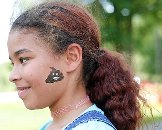 Tearra McCall, 11, of Winona, smiles after getting a poop emoji painted on her face at the Warren Walk Against Heroin at the Warren Amphitheater on Sunday. EMILY MATTHEWS | THE VINDICATOR