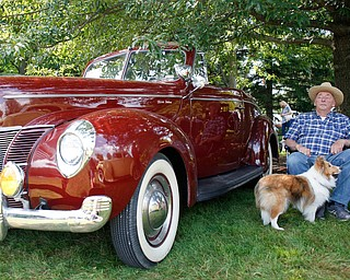 Clyde Foor, of Poland, sits next to his original 1944 Ford Deluxe with his Sheltie Piper at the 41st annual Cars in the Park car show in Boardman Park on Sunday afternoon. Proceeds from the car show will go to Harper, Foley, 4, who has Dravet Syndrome, a catastrophic form of epilepsy. EMILY MATTHEWS | THE VINDICATOR