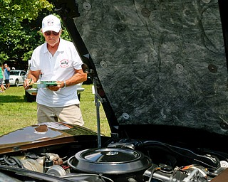 Bob Gamble, a judge at the 41st annual Cars in the Park car show, looks at a 1979 Chevrolet Corvette in Boardman Park on Sunday afternoon. Proceeds from the car show will go to Harper, Foley, 4, who has Dravet Syndrome, a catastrophic form of epilepsy. EMILY MATTHEWS | THE VINDICATOR