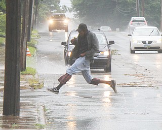William D. Lewis the vindicator A pedestrian jumps across a puddle on East Market St in Warren Tuesday afternoon shortly after a fast moving storm hit the area downing trees and dumping heavy rain.