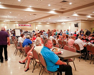Attendees of the Slovak Fest eat, mingle, and look at the Slovak basket auction at Byzantine Center at the Grove on Sunday afternoon. EMILY MATTHEWS | THE VINDICATOR