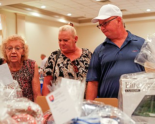 From left, Dixie Kosovec, her daughter Laurie Kosovec, and Laurie's boyfriend Mark Mound, all of McDonald, look at baskets in the Slovak basket auction at the Slovak Fest at Byzantine Center at the Grove on Sunday afternoon. EMILY MATTHEWS | THE VINDICATOR