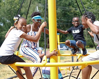 From left, Serenity Robinson, 8, Zaniyah Keaton, 13, Emmanuel Robinson, 7, and Meshua Keaton, 14, all of the East Side, play on a spinning swing at the new playground at Lincoln Knolls Community Park on Saturday.  EMILY MATTHEWS | THE VINDICATOR