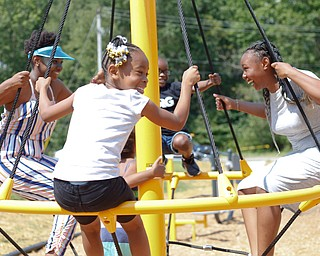 From left, Zaniyah Keaton, 13, Serenity Robinson, 8,  Emmanuel Robinson, 7, and Meshua Keaton, 14, all of the East Side, play on a spinning swing at the new playground at Lincoln Knolls Community Park on Saturday.  EMILY MATTHEWS | THE VINDICATOR