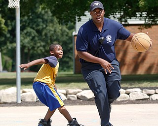 Charles Hodge, with the Youngstown Fire Department, right, plays basketball with Darnell Young, 8, of the East Side, on the newly renovated basketball court at Lincoln Knolls Community Park on Saturday.  EMILY MATTHEWS | THE VINDICATOR