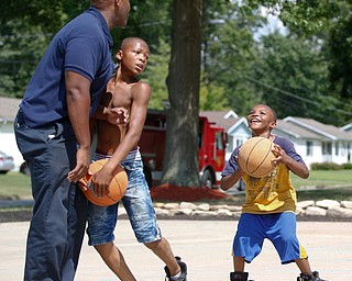 Darnell Young, 8, of the East Side, right, prepares to shoot a basket while Mandell Young, 12, of the East Side, blocks Charles Hodge, with the Youngstown Fire Department, on the newly renovated basketball court at Lincoln Knolls Community Park on Saturday.  EMILY MATTHEWS | THE VINDICATOR