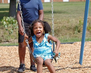 Amyre Milender, 11, pushes Aries Baity, 4, on a swing at the new playground at Lincoln Knolls Community Park on Saturday.  EMILY MATTHEWS | THE VINDICATOR