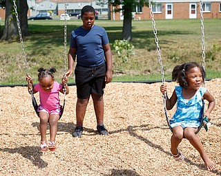 Amyre Milender, 11, center, pushes Danyla Abdullah, 2, left, and Aries Baity, 4, on the swings at the new playground at Lincoln Knolls Community Park on Saturday.  EMILY MATTHEWS | THE VINDICATOR