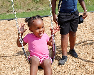 Amyre Milender, 11, right, pushes Danyla Abdullah, 2, on a swing at the new playground at Lincoln Knolls Community Park on Saturday.  EMILY MATTHEWS | THE VINDICATOR
