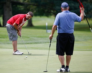 Eric Grunenwald putts the ball while Jerry Ferrell Sr., watches during the Farmers National Bank Greatest Golfer of the Valley tournament at Youngstown Country Club on Saturday. EMILY MATTHEWS | THE VINDICATOR