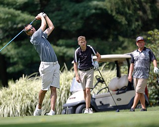 Brian Newell, left, drives the ball while Bobby Jonday, center, and David Kilgore watch during the Farmers National Bank Greatest Golfer of the Valley tournament at Youngstown Country Club on Saturday. EMILY MATTHEWS | THE VINDICATOR