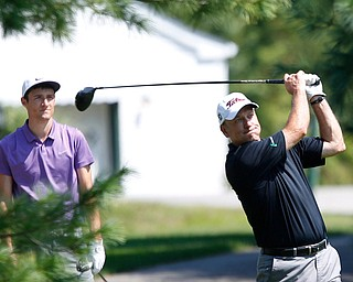 Garrett Frank drives the ball while Brandon Pluchinsky watches behind him during the final day of the Greatest Golfer tournament at the Lake Club on Sunday. EMILY MATTHEWS | THE VINDICATOR