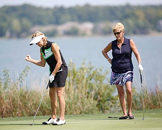 Linda Burke reacts after getting her putt in the hole while Jean Scarsella watches during the final day of the Greatest Golfer tournament at the Lake Club on Sunday. EMILY MATTHEWS | THE VINDICATOR