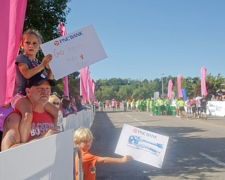 Mya Morgan, 5, of Cortland, sits on the shoulders of Tom Ayres, of Niles, while she and Chandler Ayres, 6, hold signs for Morgan's parents Andy and Ro Morgan during the 2019 Panerathon on Sunday morning. Andy finished in first for the open men's 10K with a time of 31:40.0 and Ro came in first for the open women's 10K with a time of 37:31.8. EMILY MATTHEWS | THE VINDICATOR