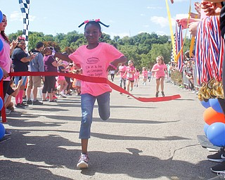 Nevaeh Taltoan, 7, of Girard, crosses the finish line first in the 7 year old girls division of the Kids Run during the 2019 Panerathon on Sunday morning. EMILY MATTHEWS | THE VINDICATOR