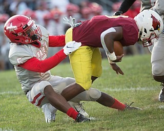 Chaney's Key-Shaun Davis tries to pull down Cardinal Mooney's Dom Byrd during their game at Rayen Stadium on Thursday. EMILY MATTHEWS | THE VINDICATOR