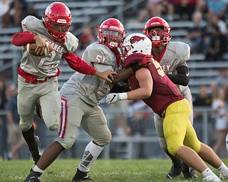 Chaney's Delshawn Petrosky runs with the ball while My'Twan Cottle (51) and Kesean Lucky try to block Cardinal Mooney's Will Skretta during their game at Rayen Stadium on Thursday. EMILY MATTHEWS | THE VINDICATOR