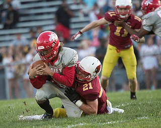 Chaney's Delshawn Petrosky gets tackled by Cardinal Mooney's Michael Pastella during their game at Rayen Stadium on Thursday. EMILY MATTHEWS | THE VINDICATOR