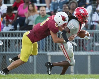 Chaney's Deron Gilbert runs with the ball while Cardinal Mooney's Michael Santisi tries to tackle him during their game at Rayen Stadium on Thursday. EMILY MATTHEWS | THE VINDICATOR