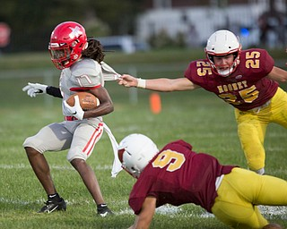 Cardinal Mooney's Jack McGlone (25) and Michael Santisi try to tackle Chaney's Deron Gilbert during their game at Rayen Stadium on Thursday. EMILY MATTHEWS | THE VINDICATOR