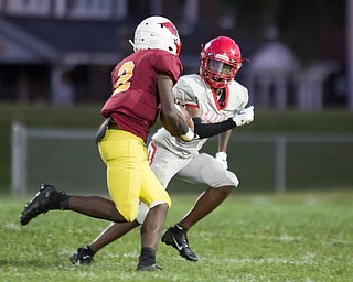 Chaney's Deron Gilbert runs with Cardinal Mooney's Zyere Rodgers during their game at Rayen Stadium on Thursday. EMILY MATTHEWS | THE VINDICATOR