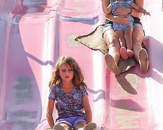 Tricia Calzo, right, of Boardman, holds her daughter Charlotte Calzo, 2, on her lap as they ride the fun slide with Charlotte's cousin Zoe Bayer, 7, at the Canfield Fair on Thursday. EMILY MATTHEWS | THE VINDICATOR